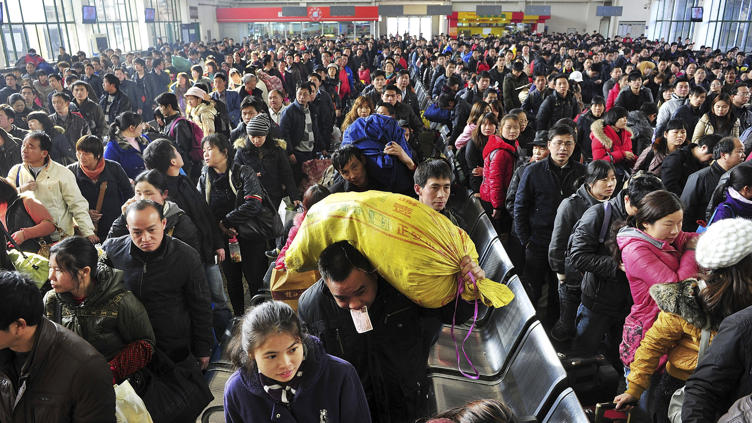 In this photo taken on Tuesday, Jan. 31, 2012, passengers wait to board trains at a railway station in Changsha, in central China's Hunan province. Millions of Chinese are expected to cram into China's train and bus network to return from home to work after the week-long Chinese Lunar New Year.