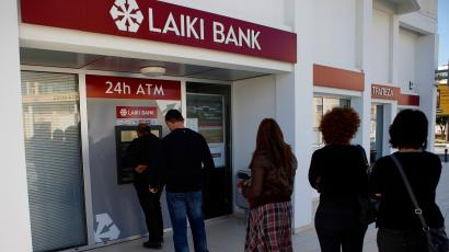 People queue to use an ATM machine outside of a Laiki Bank branch in Larnaca, Cyprus, Saturday, March 16, 2013.