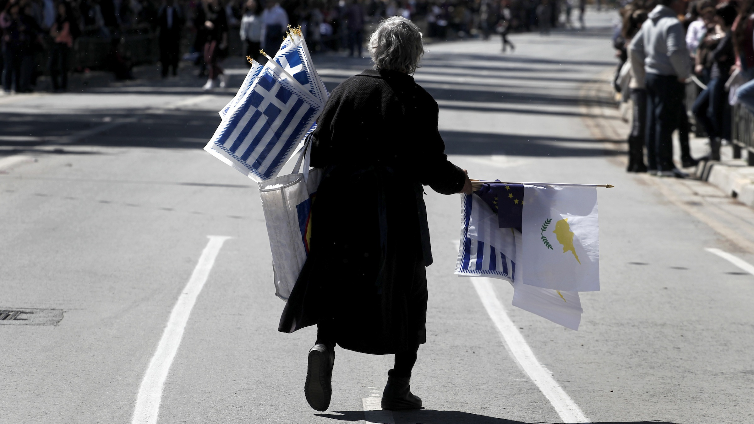 An elderly woman sells Greek, Cypriot, and EU flags before the start of a parade for Greek Independence Day celebrations in capital Nicosia, Cyprus, Monday, March 25, 2013. Cyprus secured what its politicians described as a ìpainfulî solution to avert imminent bankruptcy, agreeing early Monday to slash its oversize banking sector and make large account holders take losses to help pay to secure a last-minute euro10 billion (US$13 billion) bailout. (AP Photo/Petros Giannakouris)