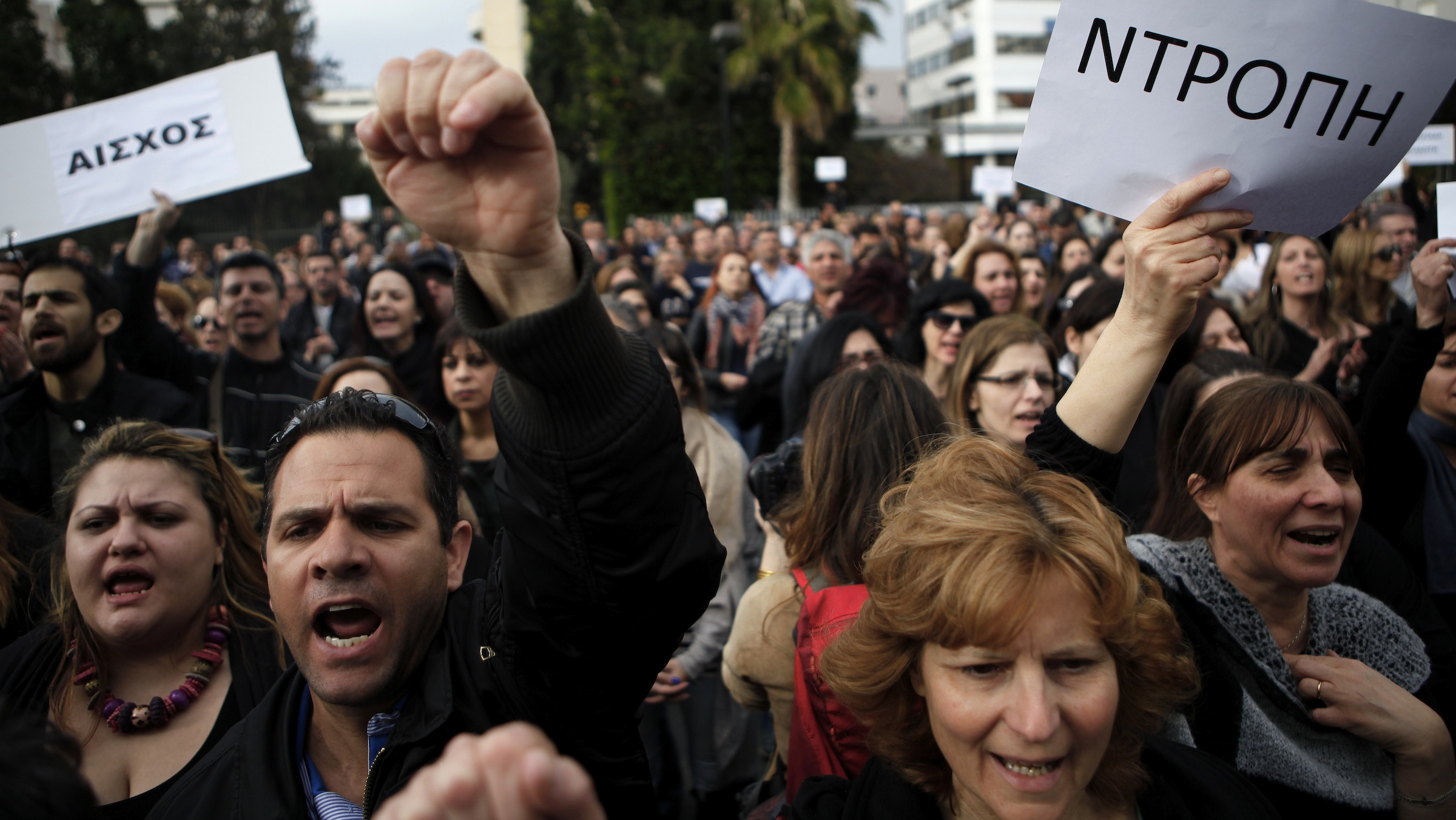 """Employees of the Bank of Cyprus shout slogans as they holds banners reading in Greek """"shame"""" during a protest at Cyprus central bank in Nicosia, Cyprus, Tuesday, March 26, 2013. Cypriot businesses were under increasing strain to keep running on Tuesday after financial authorities stretched the countryís bank closure into a second week amid fears that depositors will rush to drain their accounts. (AP Photo/Petros Karadjias)"""