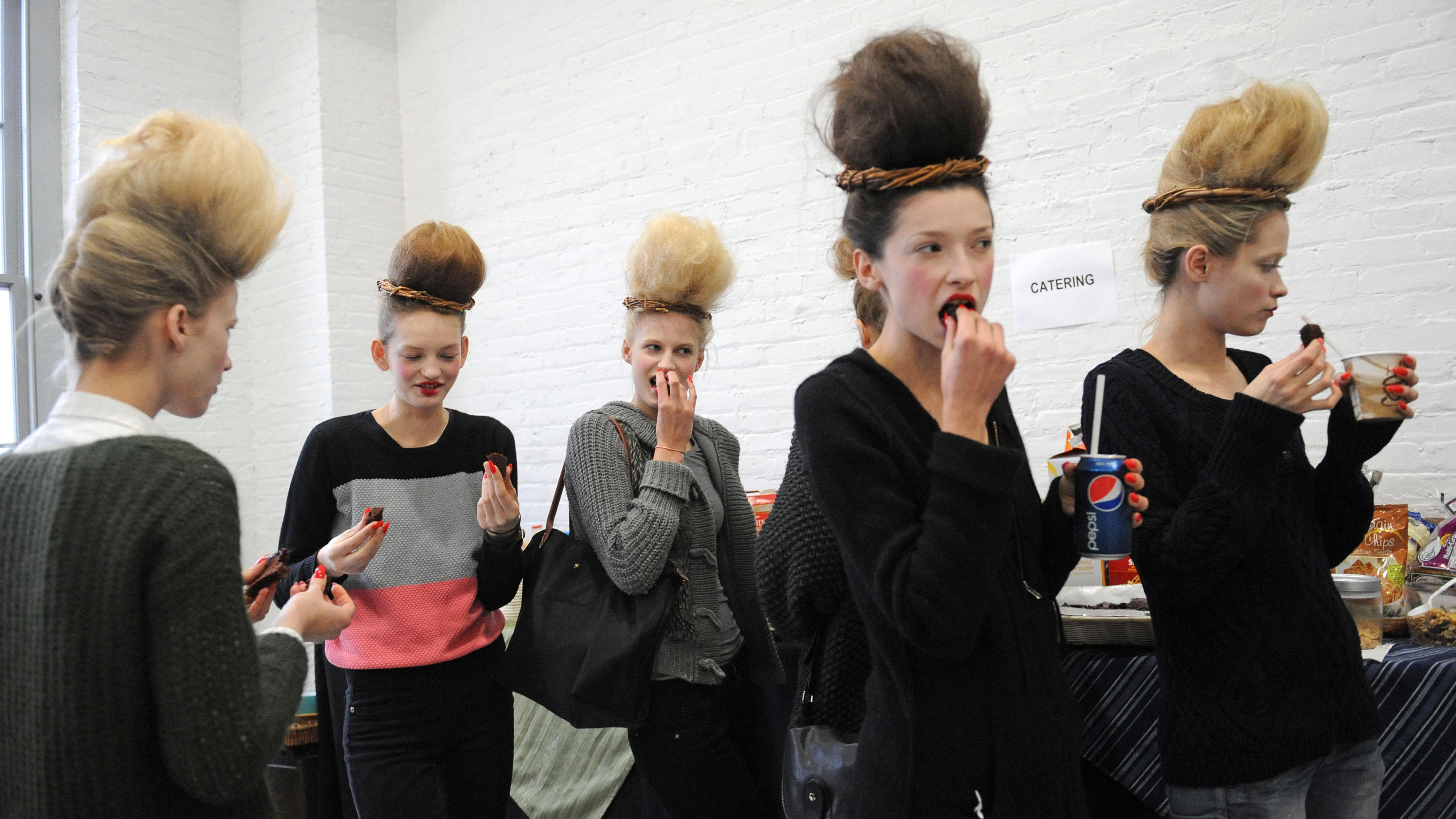 Models take a break to eat backstage before the showing of the Thom Browne Fall 2013 collection during Fashion Week, Monday, Feb. 11, 2013, in New York. (AP Photo/Louis Lanzano)