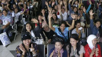 Overseas Filipino Workers, who fled the civil war in Syria, cheer upon arriving at the Ninoy Aquino International Airport via a chartered flight by the International Organization for Migration on Tuesday, Sept. 11, 2012, in Manila, Philippines. The nearly 300 workers, all of them young women who worked as babysitters and maids in Syria, said they were scared for their safety and sought shelter at the Philippine Embassy in Damascus until their repatriation Tuesday. (AP Photo/Bullit Marquez