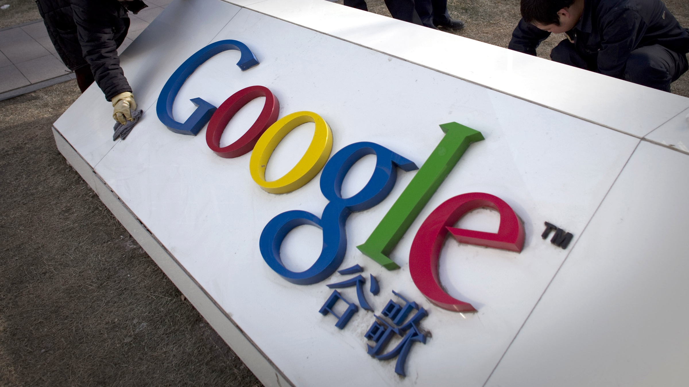 In this photo taken on Monday, Jan. 25, 2010, workers clean and repair broken part of a marble tablet bearing Google's logo in front of Google China's headquarters building in Beijing, China. Google's Android operating system should face no limits on its use by China's phone companies so long as it complies with Chinese regulations, the government said Wednesday. (AP Photo/Alexander F. Yuan)