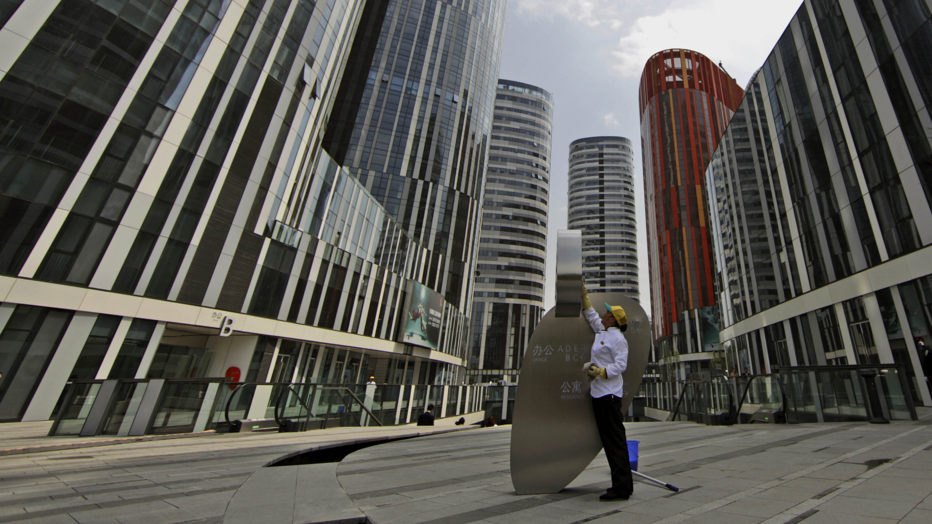 """A Chinese woman cleans a banner outside commercial and residential buildings in Beijing, China, Tuesday, May 18, 2010. Chinese Premier Wen Jiaobao commented Friday, that Beijing will act """"decisively"""" to cool surging housing prices. (AP Photo/Muhammed Muheisen)"""