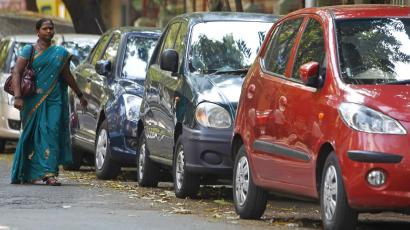 An Indian woman walks past cars parked by the roadside in Mumbai, India, Thursday, Dec. 8, 2011.Car sales in India will likely be almost flat this fiscal year, despite a 7 percent rise in sales in November, an industry group said Thursday. (AP Photo/Rafiq Maqbool