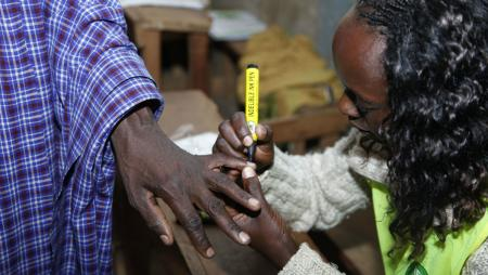 An official at the polling station put an ink mark on a Masai finger after he cased his vote.