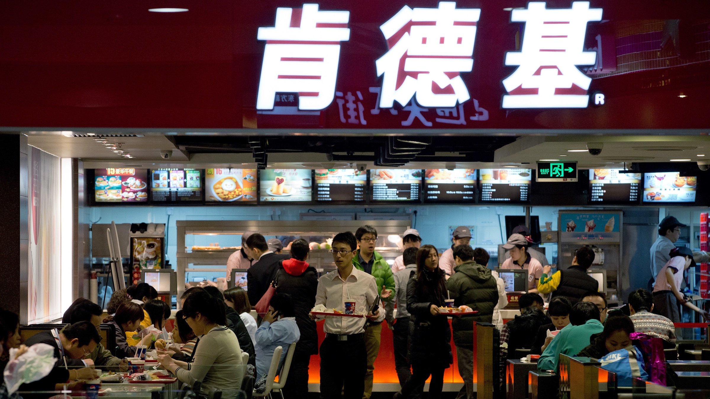 Customers buy meals at a KFC restaurant outlet at a shopping mall in Beijing Monday, Feb. 25, 2013. KFC launched a campaign Monday to rebuild its battered brand in China, promising tighter quality control after a scandal over misuse of drugs by its poultry suppliers. (AP Photo/Andy Wong)