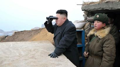 In this March 7, 2013 photo released by the Korean Central News Agency (KCNA) and distributed March 8, 2013 by the Korea News Service, North Korean leader Kim Jong Un, center, uses binoculars to look at the South's territory from an observation post at the military unit on Jangjae islet, located in the southernmost part of the southwestern sector of North Korea's border with South Korea.