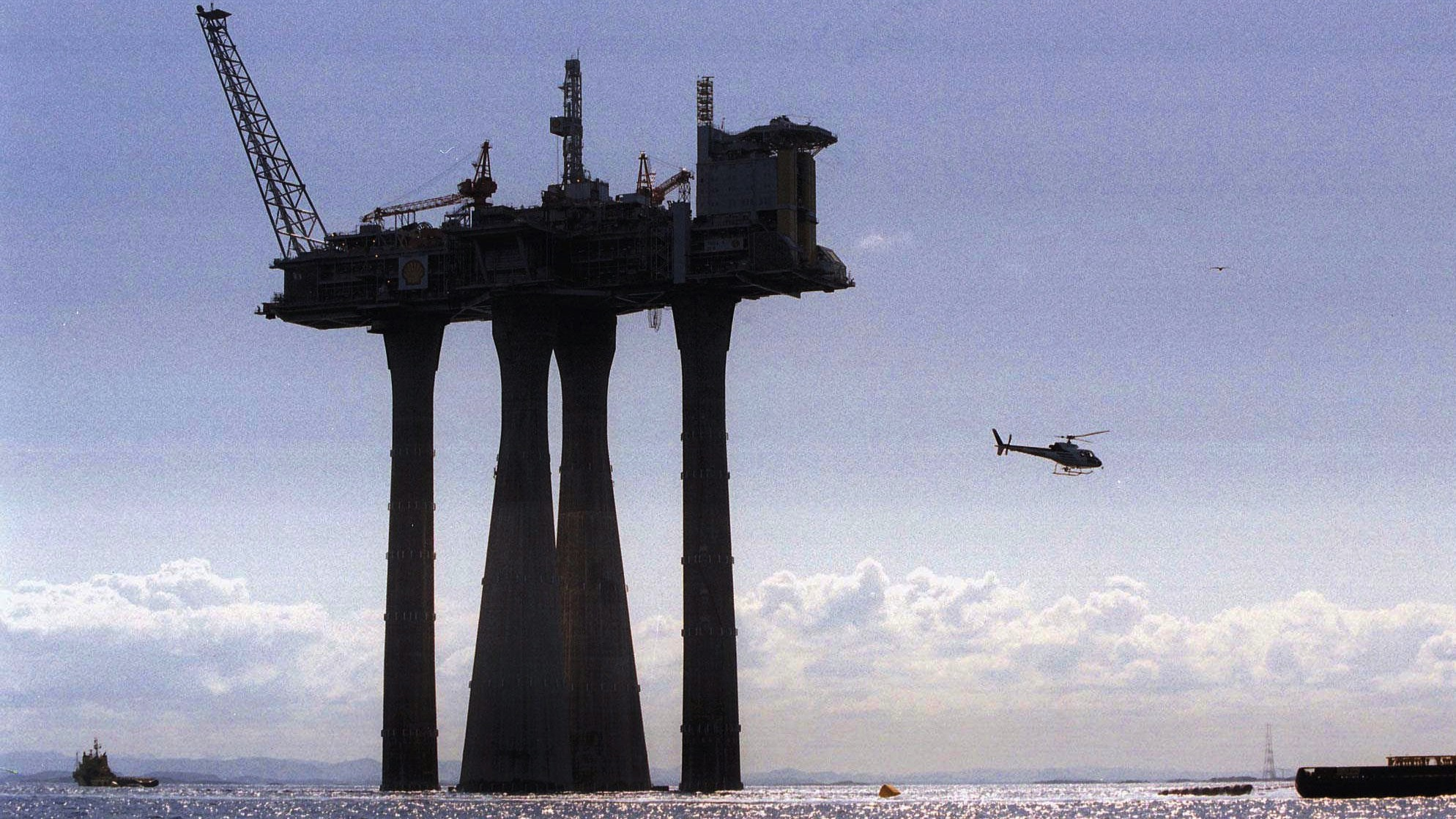 """The world's largest concrete construction, the gas platform """"Troll"""", dwarfs everything around when being towed out into the North Sea from Stavanger Thursday May 11, 1995. (AP Photo/ Morten Hval)"""