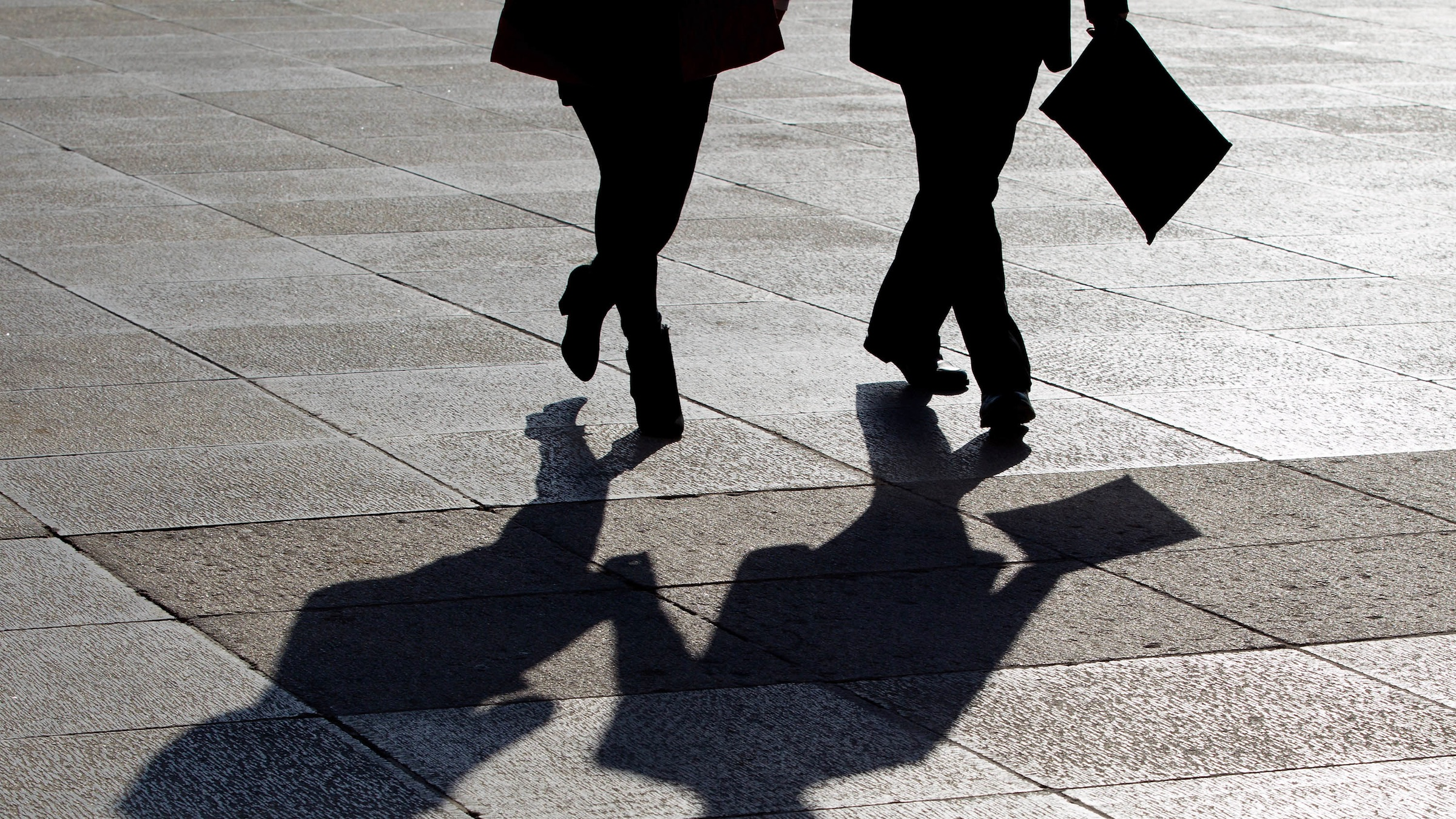 Delegates cast their shadow on the floor as they arrives to attend a plenary session of the National People's Congress held at the Great Hall of the People in Beijing Sunday, March 10, 2013. During the session, the Cabinet unveiled its plan to streamline government ministries, doing away with the powerful Railways Ministry and creating a super-agency to regulate the media and realigning other bureaucracies in a bid to boost efficiency. (AP Photo/Andy Wong)