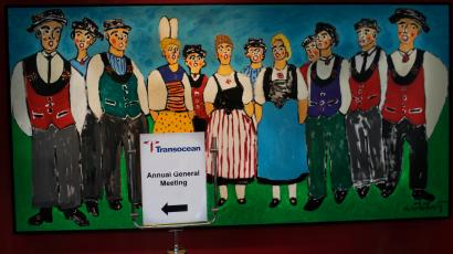 A sign for the Transocean annual general meeting in front of a painting of Swiss peasants.