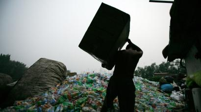 In this photo taken Tuesday, Aug. 18, 2009, a man prepares to dump plastic bottles at a trash recycling center in Beijing, China. Garbage is piling up everywhere in China, posing problems for public health and people's livelihoods in a less savory measure of the country's rapid burst from poverty to prosperity. (AP Photo/Greg Baker