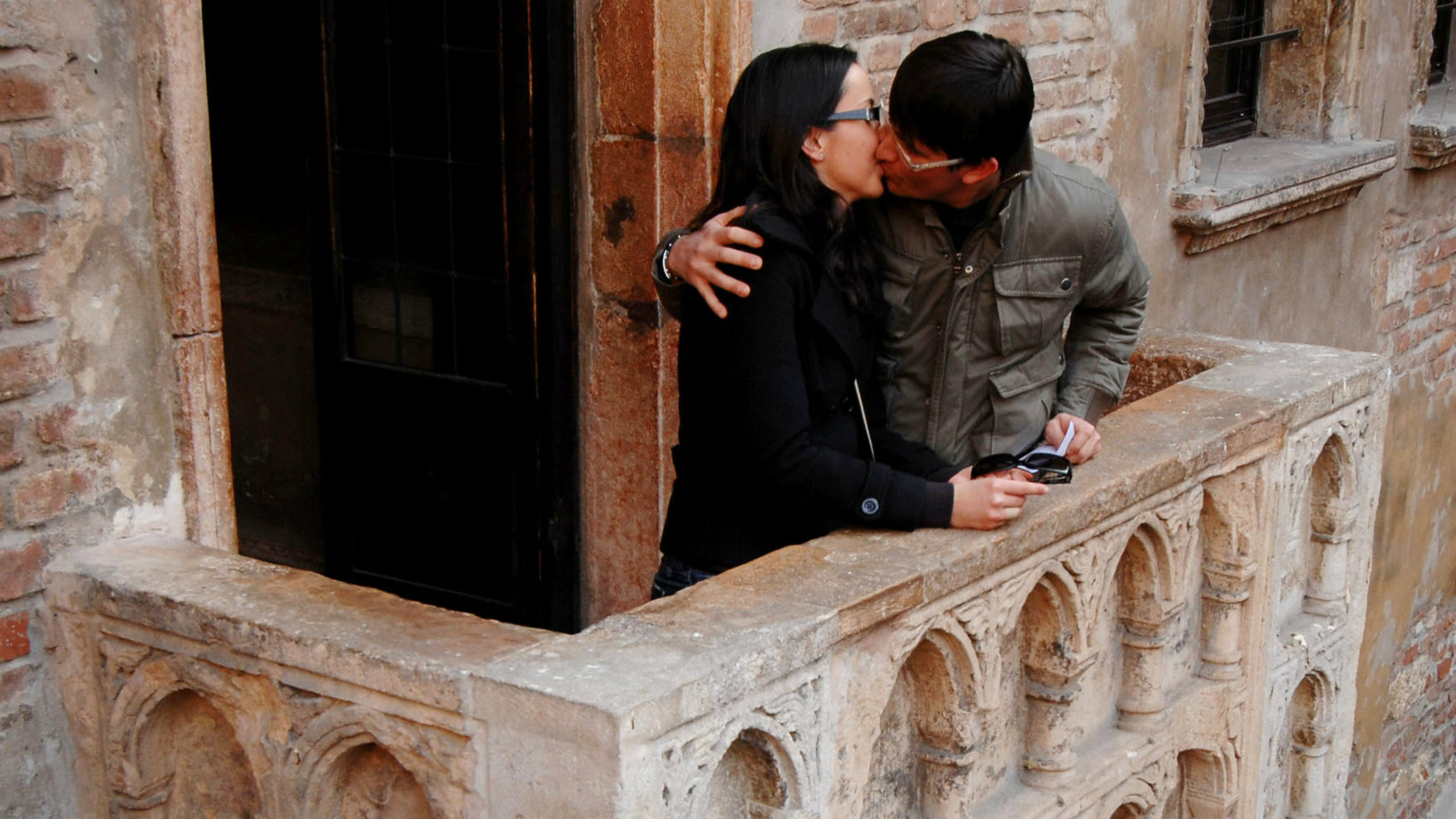 """A couple kiss on a balcony in Verona, the setting for William Shakespeare's """"Romeo and Juliet,"""" which famously pondered """"what's in a name."""""""