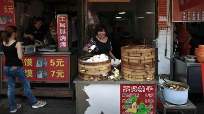 A vendor arrange buns for sale at her store along a gourmet street in Shanghai, China Sunday, May 15, 2011. The headlines are unrelenting: toxic bean sprouts, filthy oil, drug-tainted pork. For months, Chinese media have been churning out a queasy-making multitude of stories about the dangers lurking in the nation's dinner bowls. (AP Photo/Andy Wong