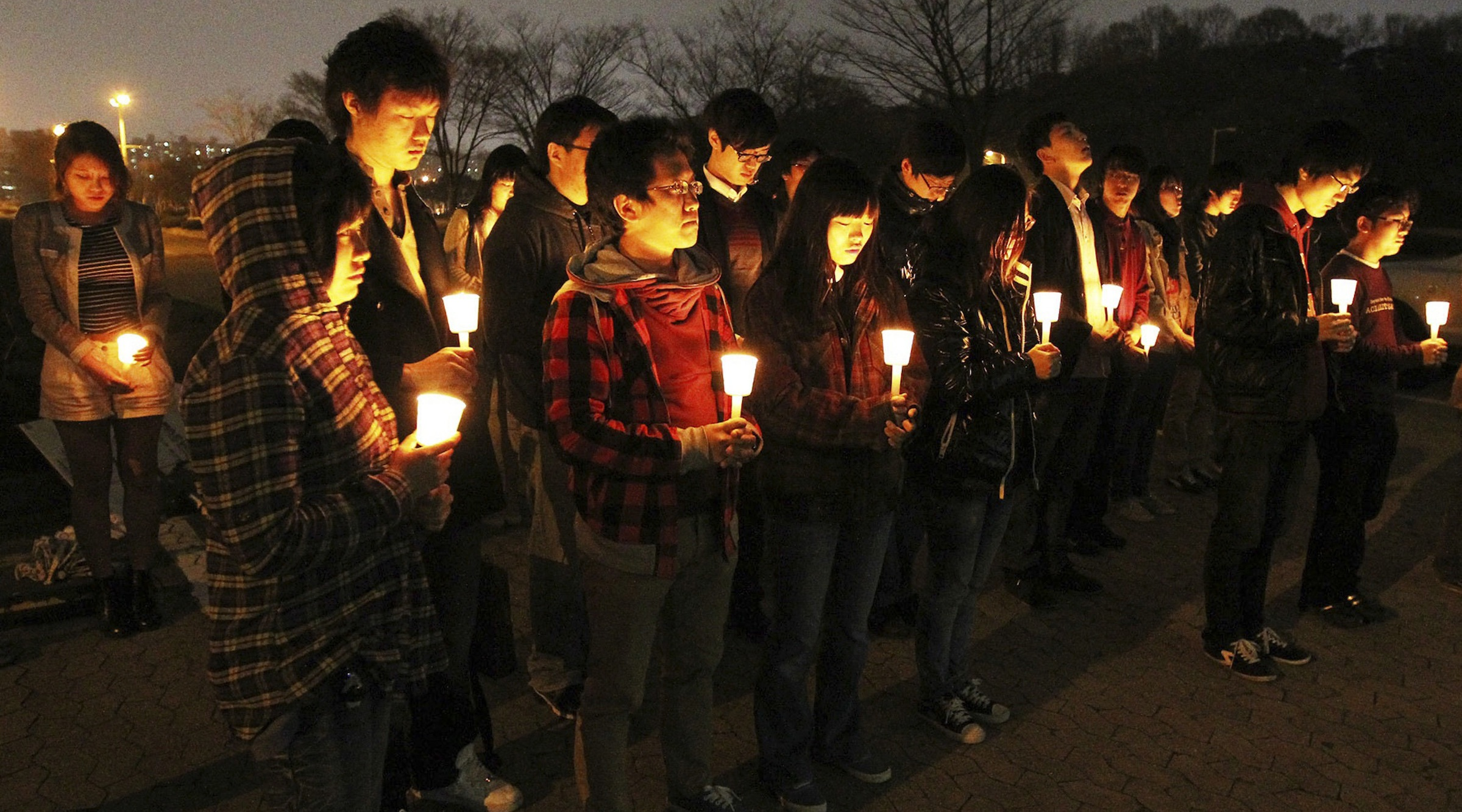 In this photo taken Sunday, April 10, 2011. Students of the Korea Advanced Institute of Science and Technology light candles to mourn for their fellow students committed suicide at their campus in Daejeon, South Korea. (AP Photo/Yonhap)   KOREA OUT