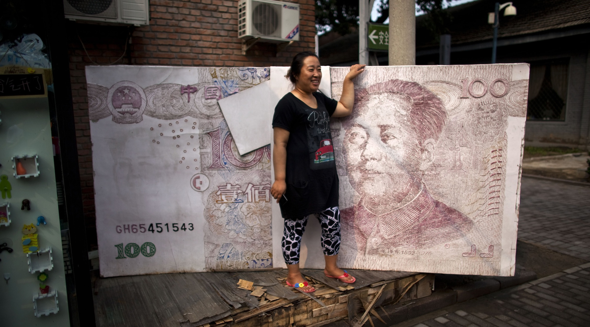 In this Aug. 26, 2011photo, a woman poses for photos with an art installation showing a stack of renminbi banknotes in Beijing, China. Regulators reportedly are expanding controls over China's banks to keep pace with a fast-changing industry and curb a credit boom as Beijing fights surging inflation. (AP Photo/Alexander F. Yuan)