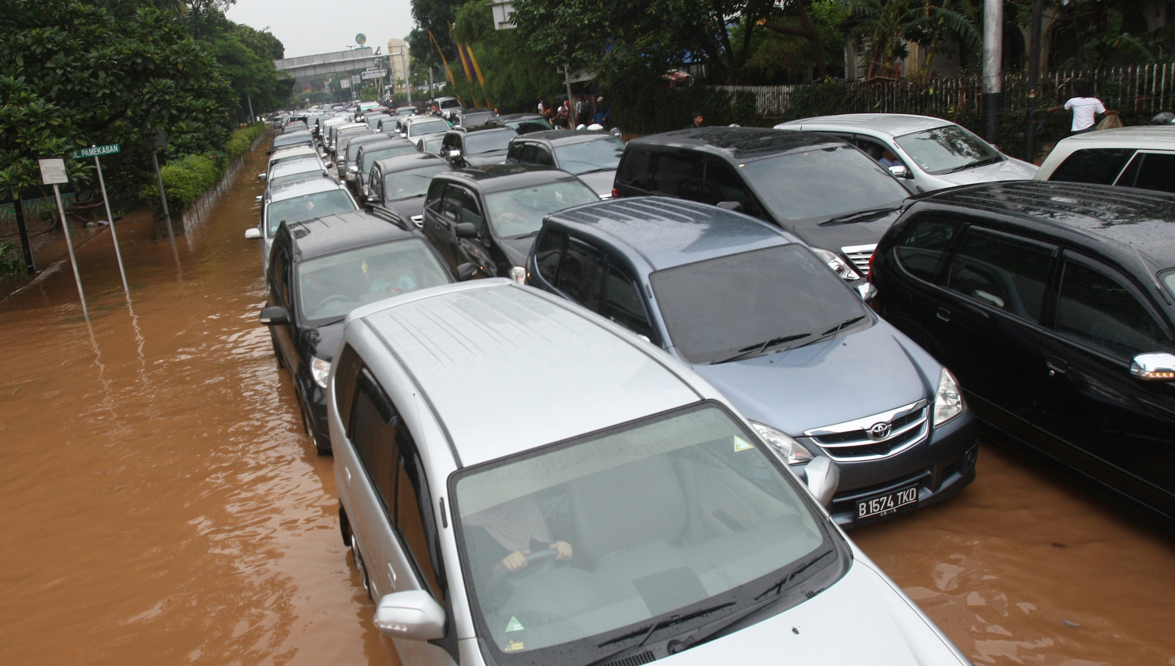Traffic on  through a flooded street in Jakarta, Indonesia Friday, Jan. 18, 2013. Indonesia's army deployed rubber boats in the capital's business district on Thursday to rescue people trapped in floods that inundated much of the city of 14 million people.(AP Photo/Achmad Ibrahim)