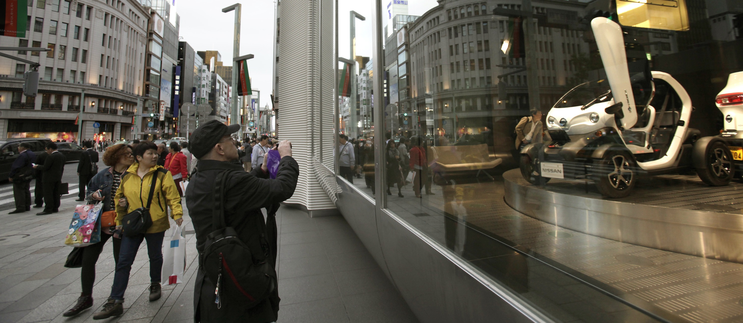 A man takes a picture of NISSAN New Mobility CONCEPT car in Nissan showroom at Ginza shopping district in Tokyo, Wednesday, April 3, 2013. (AP Photo/Shizuo Kambayashi)