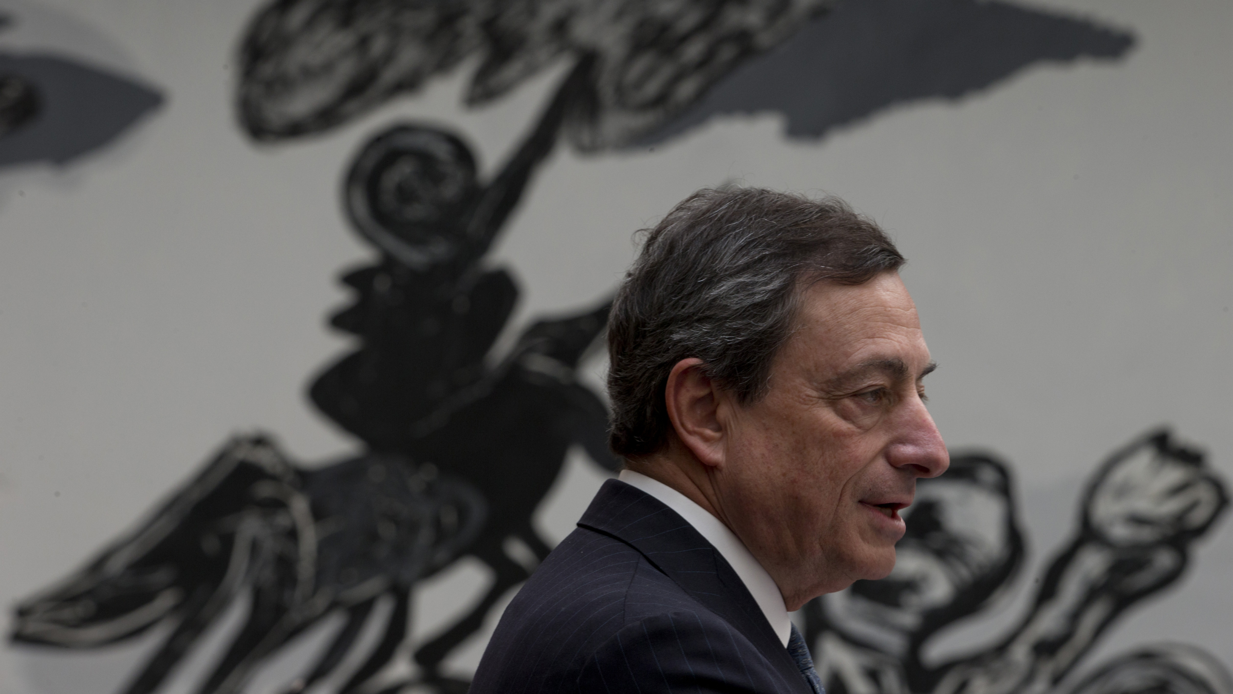 """A work of art is seen in the background as European Central Bank President Mario Draghi addresses students during a session of """"Room for Discussion"""" at the Faculty of Economics of the UvA, or University of Amsterdam, Netherlands, Monday April 15, 2013. (AP Photo/Peter Dejong)"""