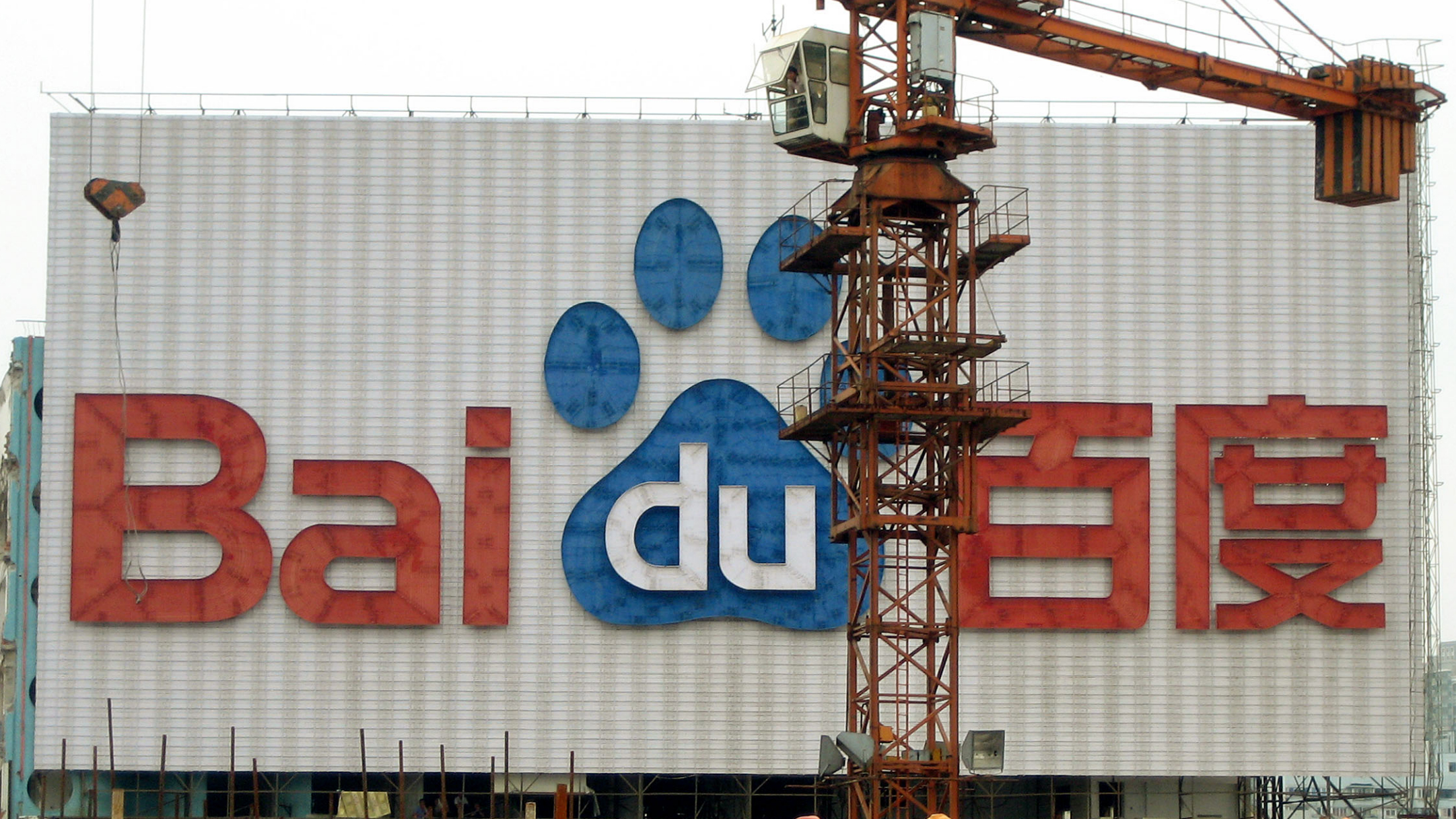 Workers rest in front of an advertisement of Baidu June 27, 2006 in Shanghai, China. Beijing-based Internet search engine Baidu.com Inc. on Wednesday, Feb. 14, 2007 said fourth-quarter net income increased fivefold as online marketing revenue more than doubled. (AP Photo/Elaine Kurtenbach