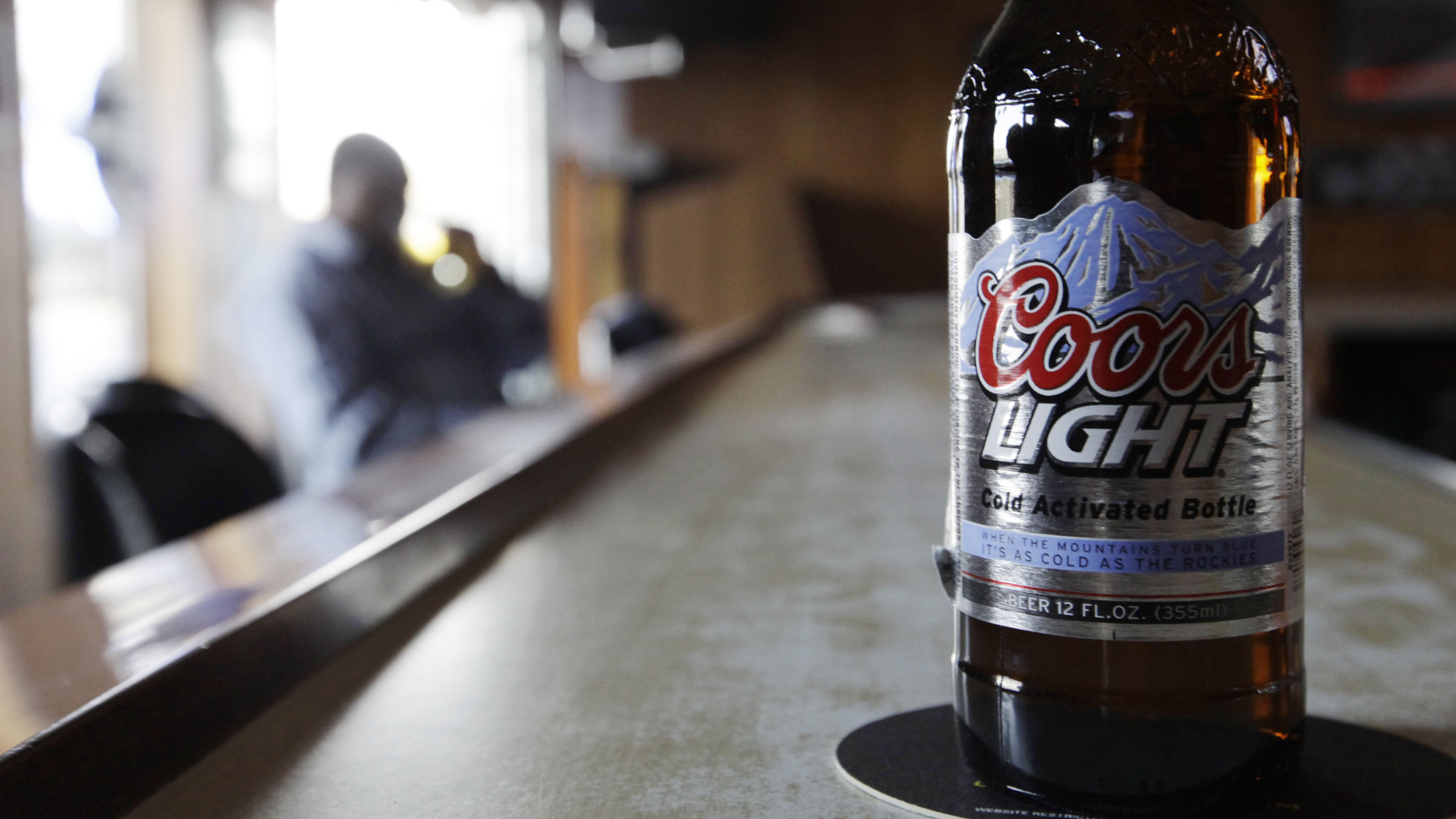 A Coors Light sits on the bar as a patron sips a beer at a tavern Monday, May 4, 2009, in Blue Island, Ill. Molson Coors Brewing Co. and SABMiller PLC said Tuesday that the first-quarter profit for their U.S. joint venture MillerCoors LLC rose 51 percent as sales of Coors Light and other brands were helped by higher prices and fewer promotions. (AP Photo/M. Spencer Green