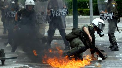 Riot police try to escape from a Molotov cocktail in central Athens, Wednesday, May 5, 2010. Greek fire officials say three people have died in a blaze that broke out at an Athens bank during rioting over government austerity measures. An estimated 100,000 people took to the streets Wednesday during a nationwide wave of strikes against spending cuts aimed at saving the country from bankrupty