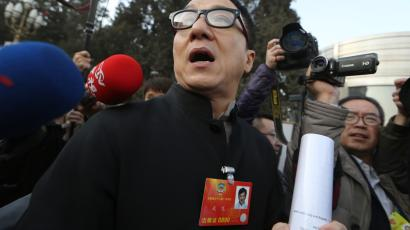 Hong Kong movie star Jackie Chan leaves after the opening session of the Chinese People's Political Consultative Conference in Beijing's Great Hall of the People, China, Sunday, March 3, 2013. (AP Photo/Kin Cheung