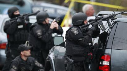 Police in tactical gear surround an apartment building while looking for a suspect in the Boston Marathon bombings in Watertown, Mass., Friday, April 19, 2013. The bombs that blew up seconds apart near the finish line of the Boston Marathon left the streets spattered with blood and glass, and gaping questions of who chose to attack and why. (AP Photo/Charles Krupa