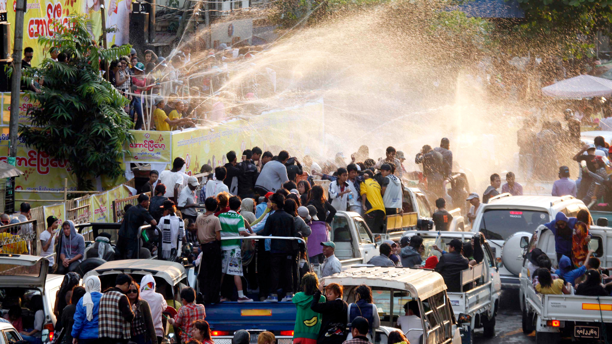 Vehicles carrying revelers line up towards a pavilion sprayed water during the traditional Thingyan celebrations in Yangon, Myanmar, Sunday, April 14, 2013. Myanmar celebrated its annual water festival, known as Thingyan, from Saturday, marking the start of the New Year according to the traditional Buddhist calendar.