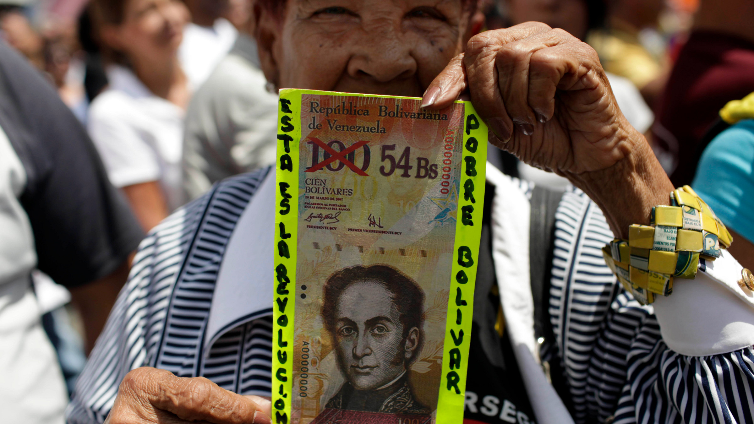 "A protester shows a fake bill that reads in Spanish ""This is the revolution. Poor Bolivar"" with the value of 100 crossed out and 54 written next to it, at an opposition demonstration against of the devaluation of the currency in Caracas, Venezuela, Saturday, Feb. 23, 2013."