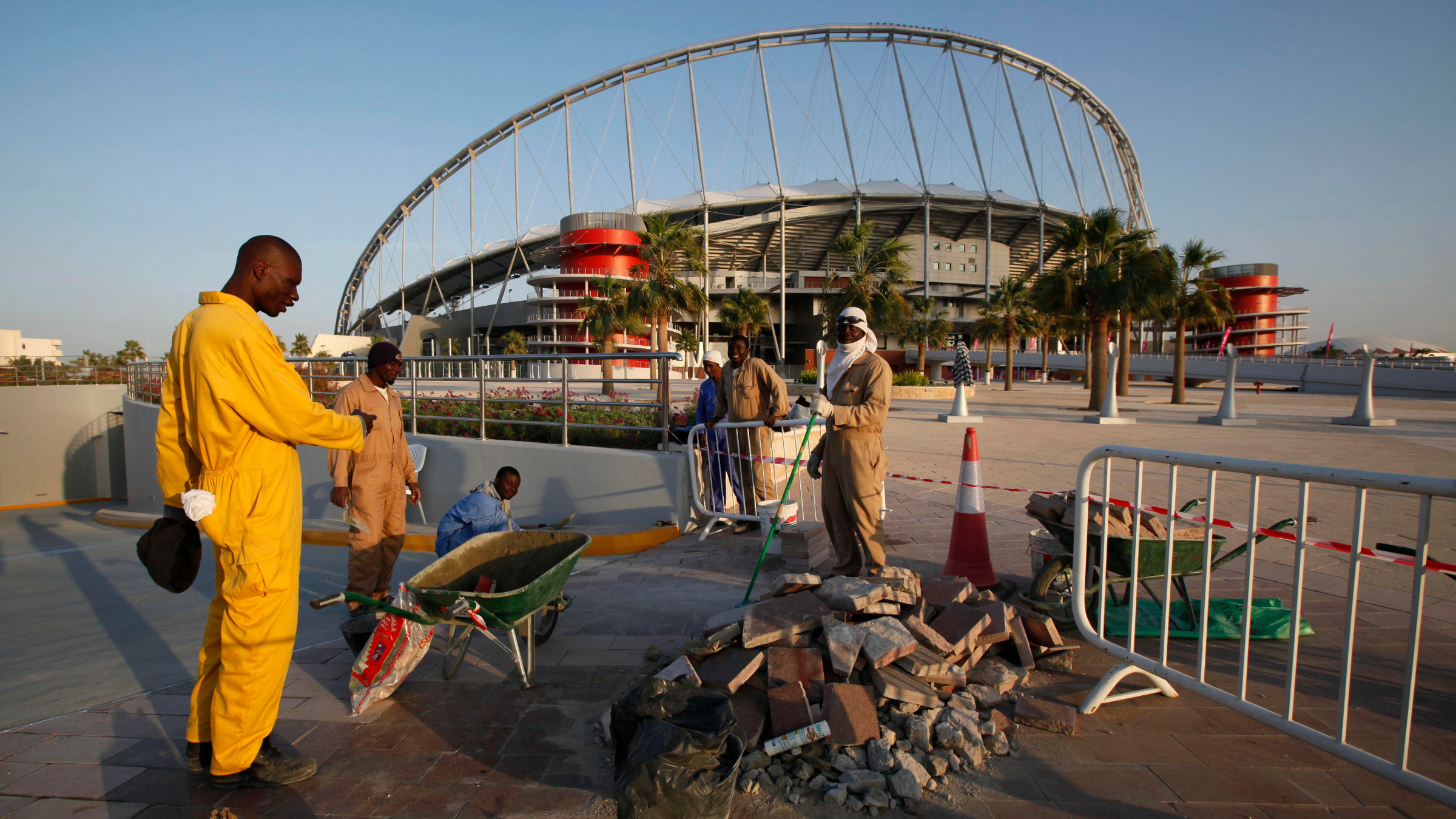 Workers clean up the road outside the Khalifa stadium where the first match of the AFC Asian Cup will take place, in Doha, Qatar, Monday, Jan. 3, 2011.
