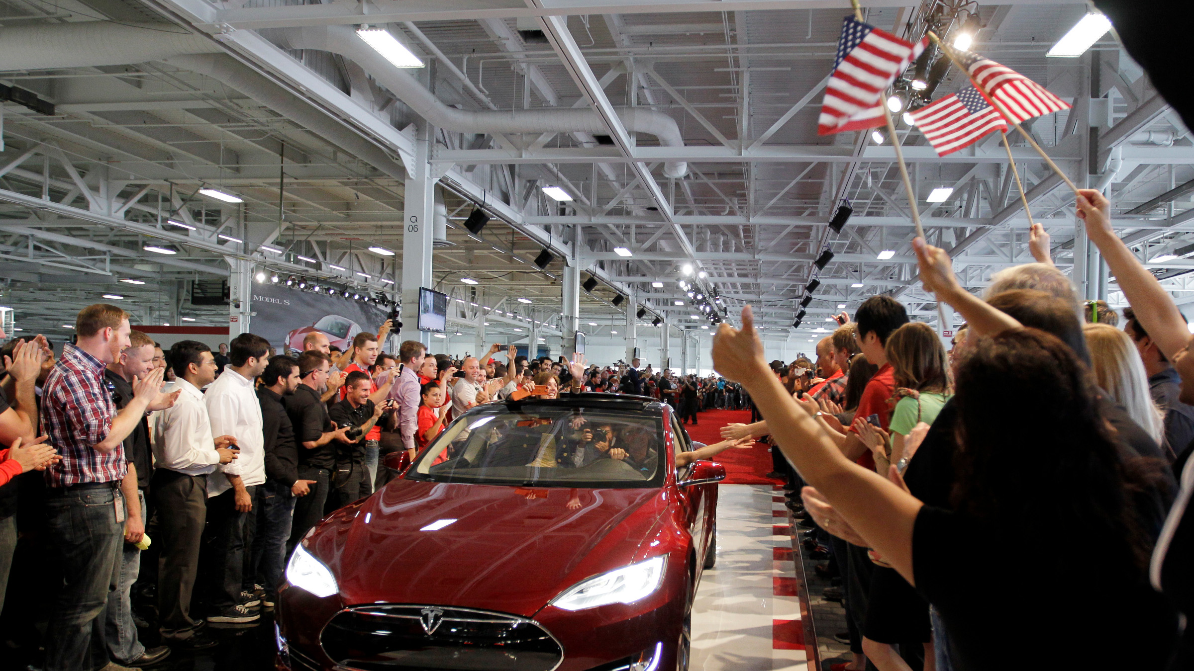 Tesla workers cheer on one the first Tesla Model S cars sold during a rally at the Tesla factory in Fremont, Calif., Friday, June 22, 2012. The first mass-market sedans offered by electric car maker Tesla are now on the road.