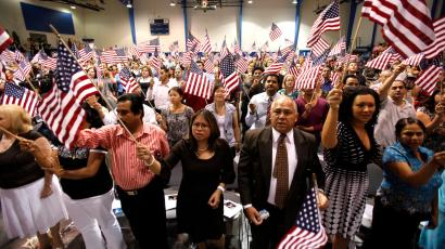 People hold flags as they are sworn in as U.S. citizens during a naturalization ceremony on Tuesday, July 2, 2010 in Phoenix.