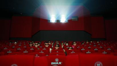 Patrons watch a 3D IMAX movie at a theater of Wanda cinema run by Dalian Wanda Group Co. in Beijing, China, Monday, May 21, 2012. The Chinese conglomerate, Dalian Wanda Group Co. announced Monday it will buy major U.S. cinema chain, AMC Entertainment Holdings, for $2.6 billion to create the world's biggest movie theater operator. (AP Photo/Ng Han Guan