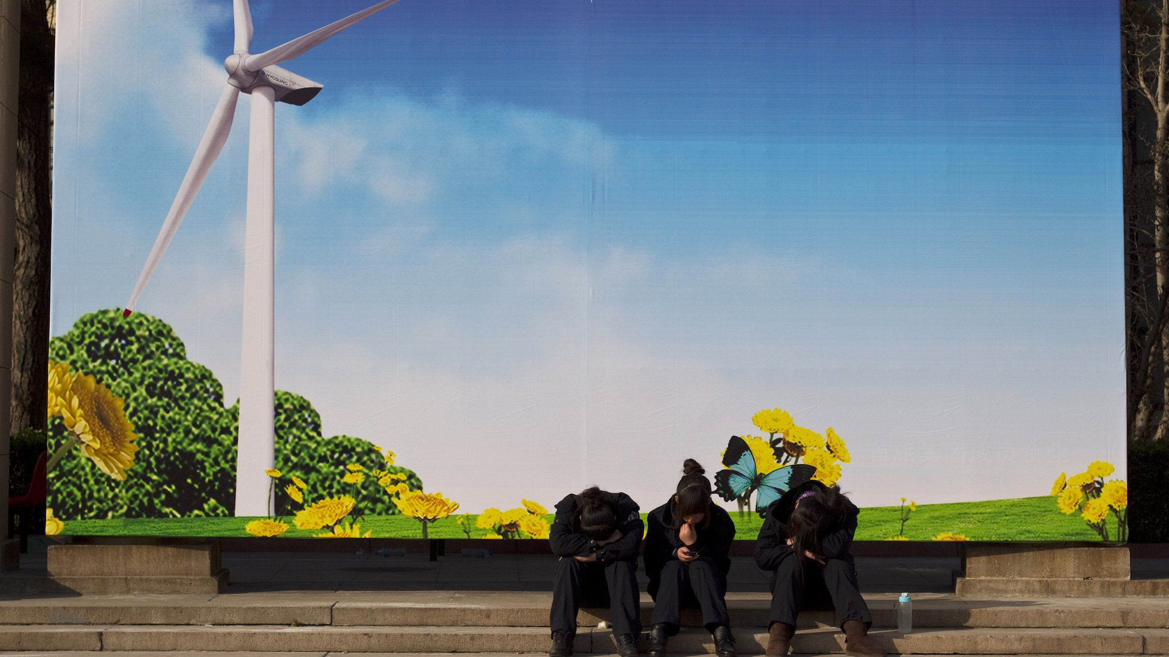 Workers rest on steps near an advertisment board showing a wind turbine outside the venue of a green industry expo in Beijing, China, Thursday, Nov. 25, 2010. (AP Photo/Alexander F. Yuan)