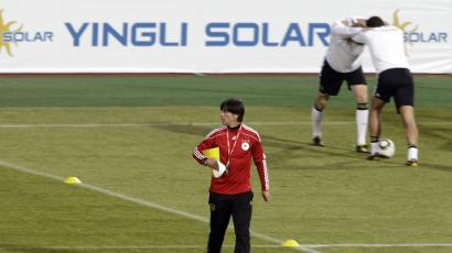 In this file photo taken Tuesday, June 22, 2010, Germany head coach Joachim Loew, front, walks over the pitch as German players stretch during a German team training session near a advertisement panel for Yingli Solar at the Super stadium in Atteridgeville near Pretoria, South Africa. China did not qualify for the World Cup, but the country is still making an appearance in South Africa. An ambitious Chinese solar company, the country's first World Cup sponsor, has placed advertising in all the stadiums in a bid to give its brand a worldwide boost. Yingli Green Energy Co.'s sponsorship deal allows it to show its logo of Yingli Solar, in Chinese and English, on electronic perimeter-boards at all 64 games of the World Cup. (AP Photo/Gero Breloer