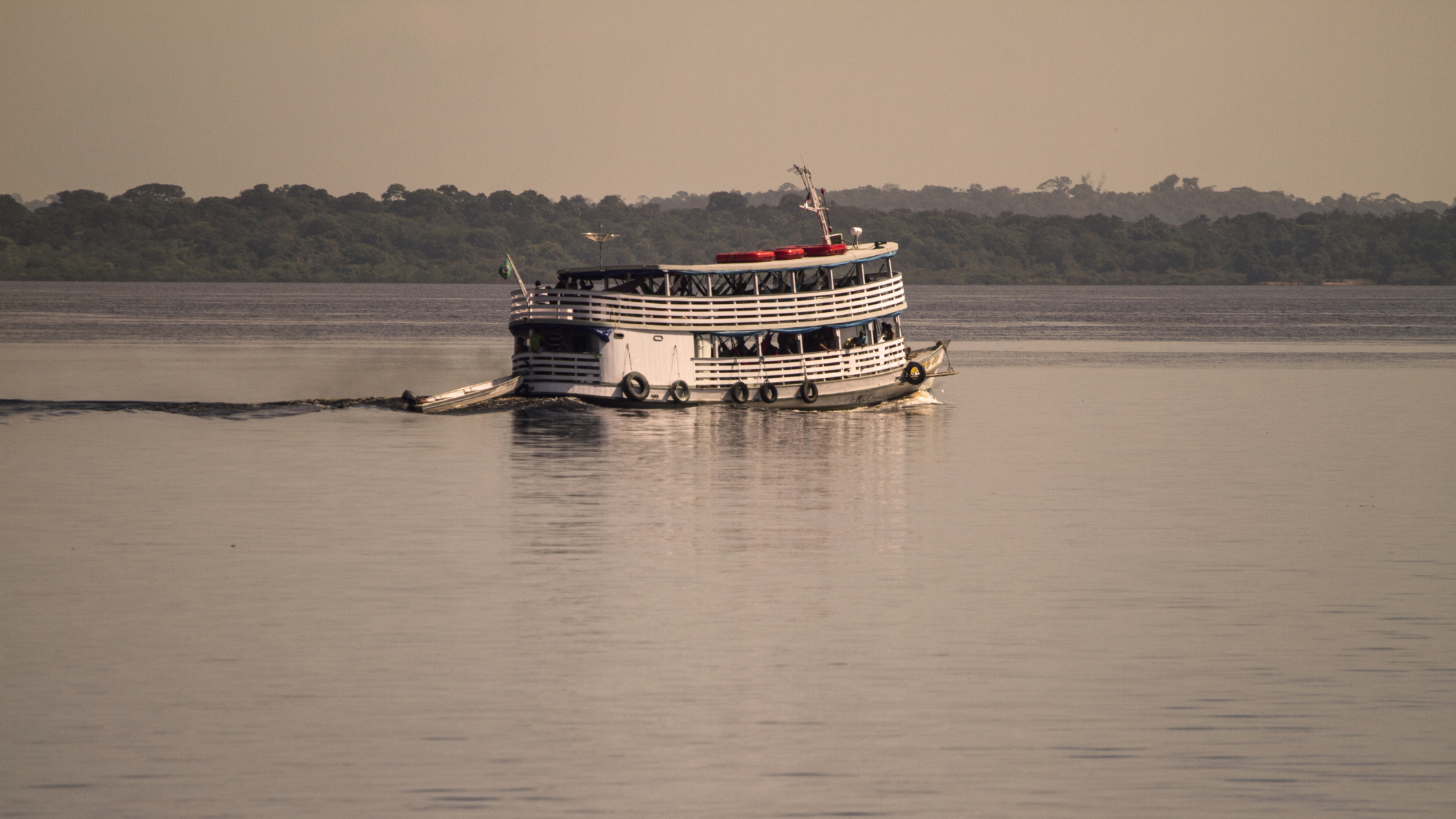 Boat of tourists sailing in Black River (Rio Negro). The Black River is the largest left tributary of the Amazon and the largest blackwater river in the world. (Brazil) By: Miguel Pereira