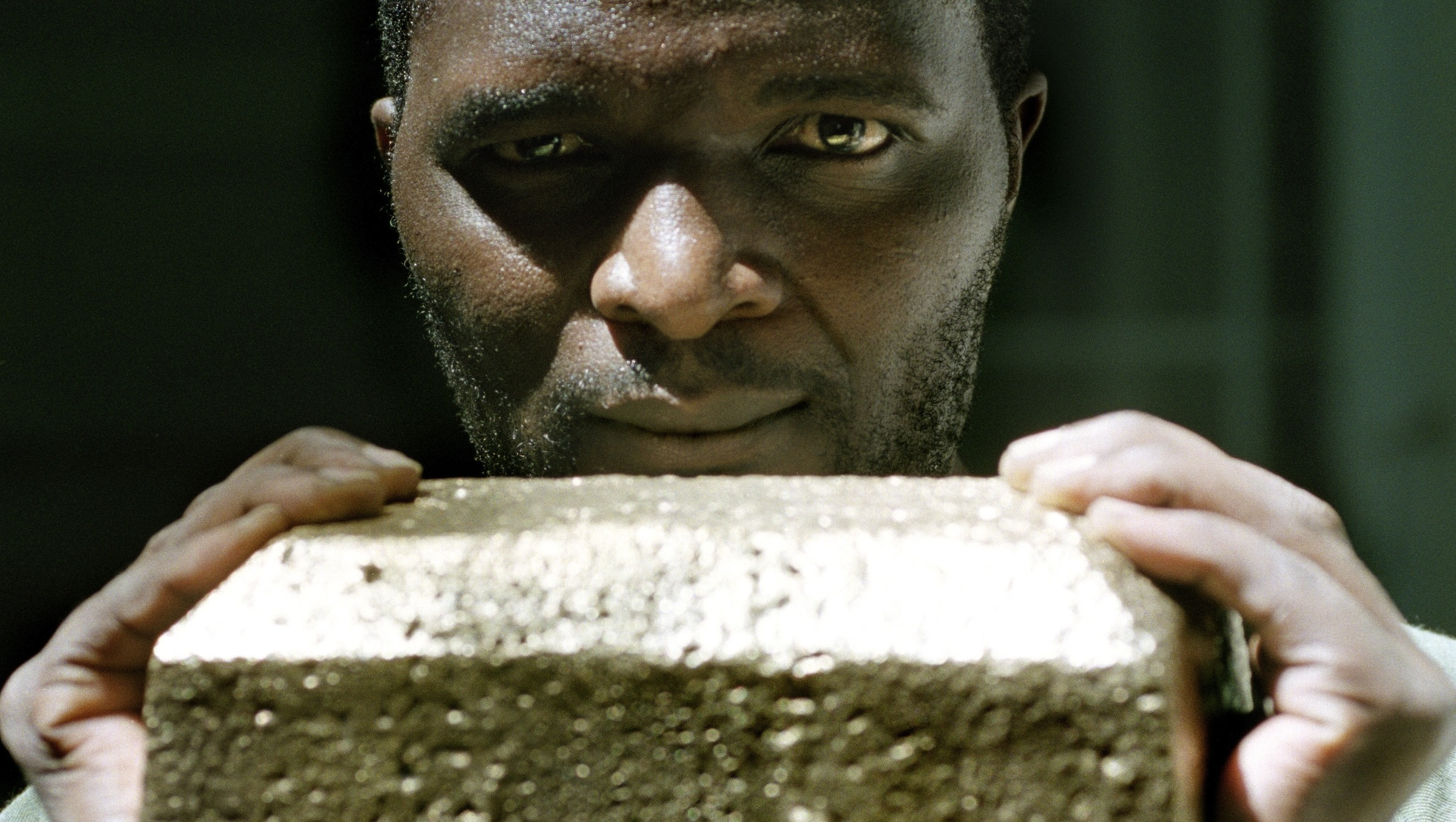 South African miner holding gold bar