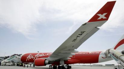 Visitors walk next to Air Asia X's new Airbus A330 aircraft during a ceremony at the Kuala Lumpur International Airport's low cost air carrier terminal in Sepang, Malaysia, Tuesday, Sept. 18, 2007. Malaysia's long-haul budget airline AirAsia X plans to sell a 20-percent stake in the company to private in for US$80 million (56 million) to raise cash for its expansion, a media report said Wednesday. (AP Photo/Vincent Thian