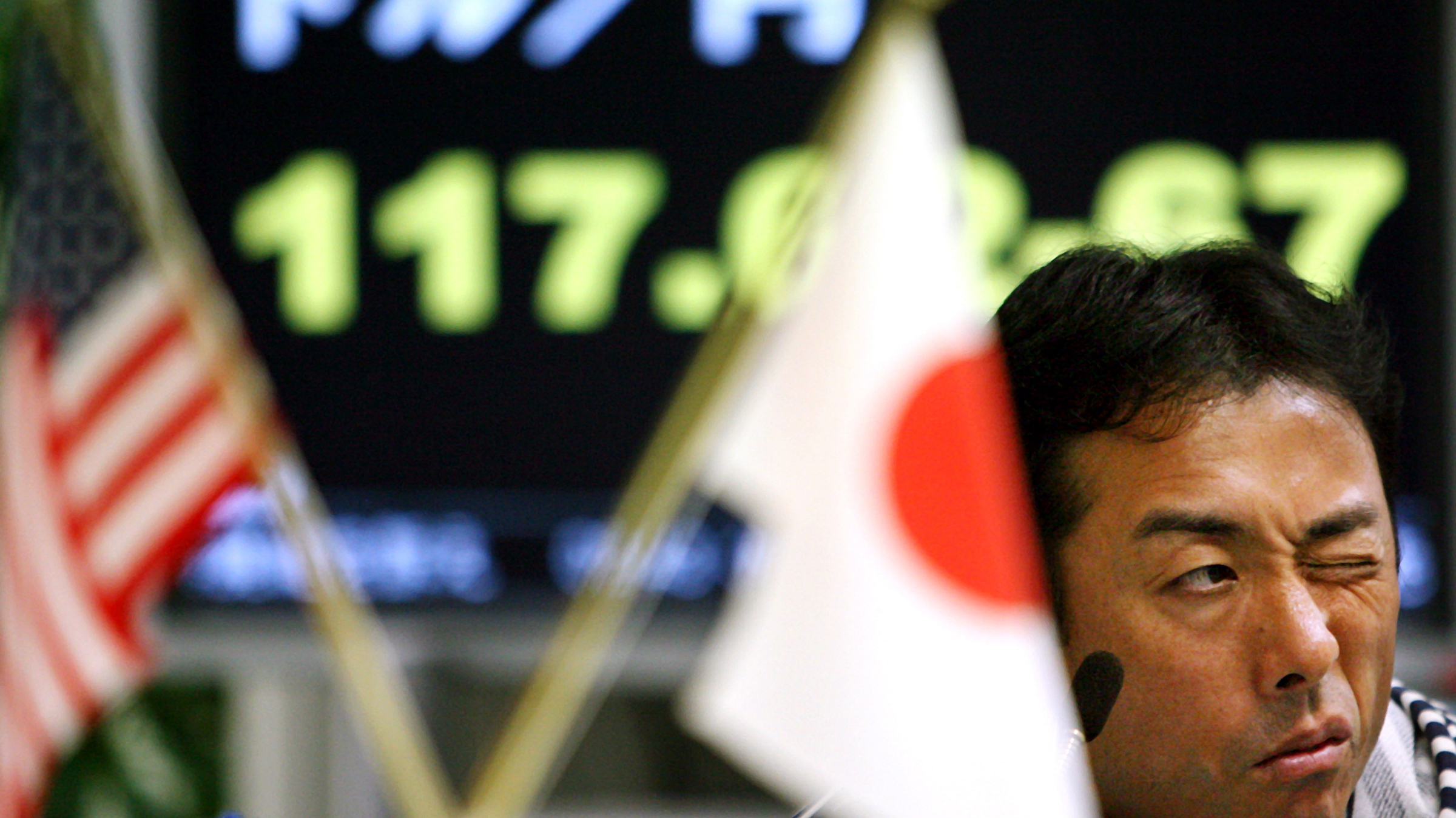 A currency trader takes in calls from clients for orders at a money brokerage in Tokyo as the U.S. dollar was trading at 117 yen level, down from 118.41 yen late Friday in New York Monday, Aug 6, 2007. (AP Photo/Junji Kurokawa)