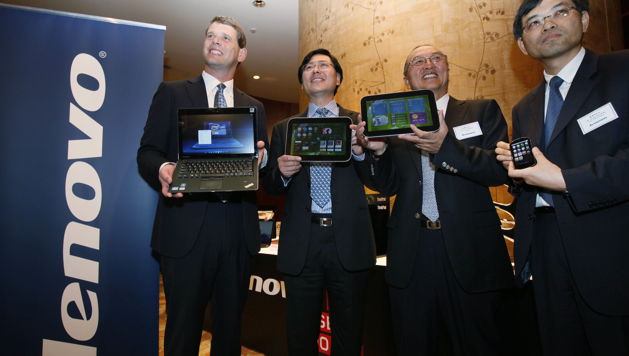From left, Rory Read, President and Chief Operating Officer of Lenovo Group Limited, Yang Yuanqing, Chief Executive Officer, Liu Chuanzhi, Chairman of the board and Wong Wai Ming, Chief Financial Officer, show their company products before the company results announcement in Hong Kong Thursday, May 26, 2011. Lenovo Group, the fourth-largest personal computer maker, says its 2010 profit more than doubled as global demand rebounded. Lenovo said Thursday it earned $273 million last year, or $2.73 per share. Global sales rose 30 percent to $21.6 billion.  (AP Photo/Kin Cheung)
