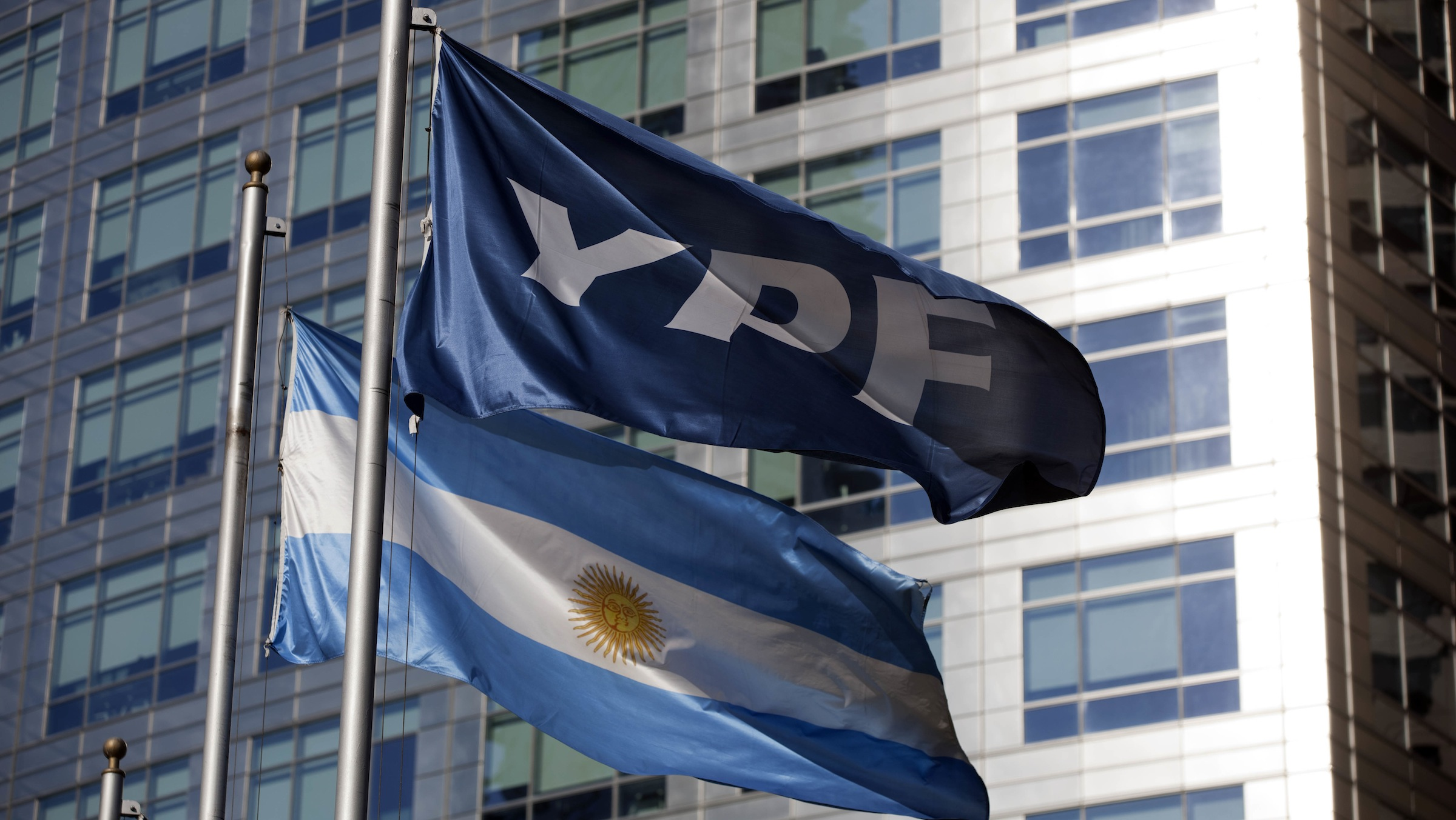 An Argentine flag, bottom, and a flag of the YPF oil company flutter in front of the YPF headquarters in Buenos Aires, Argentina, Monday, April 16, 2012. Argentine President Cristina Fernandez on Monday proposed a bill to expropriate 51 percent of the shares of YPF oil company that is controlled by Spain's Repsol, moving ahead with the plan despite fierce opposition from Madrid. (AP Photo/Natacha Pisarenko)