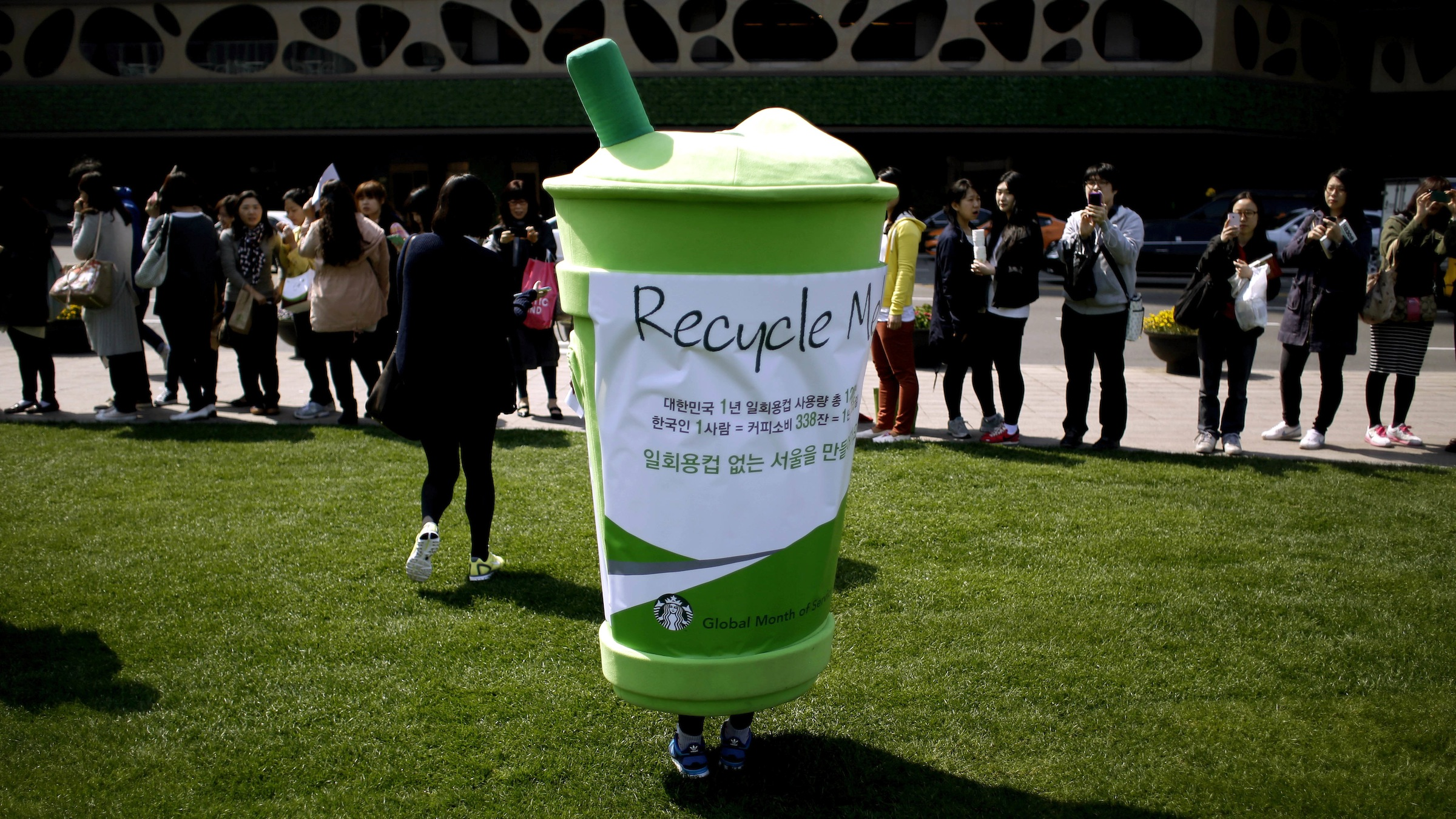 A volunteer wearing a doll of disposable cup, stands during an environment campaign as part of Earth Day celebrations in front of Seoul City Hall in Seoul, South Korea, Monday, April 22, 2013. (AP Photo/Lee Jin-man)
