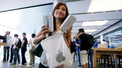 A customer shows her new iPhone 5 at the Apple store in Hong Kong Friday, Sept. 21, 2012. Apple fans lined up overnight in Australia while in Hong Kong they registered online for a chance to buy the iPhone 5, the latest version of the high-tech juggernaut's iconic smartphone, as soon as it went on sale on Friday.