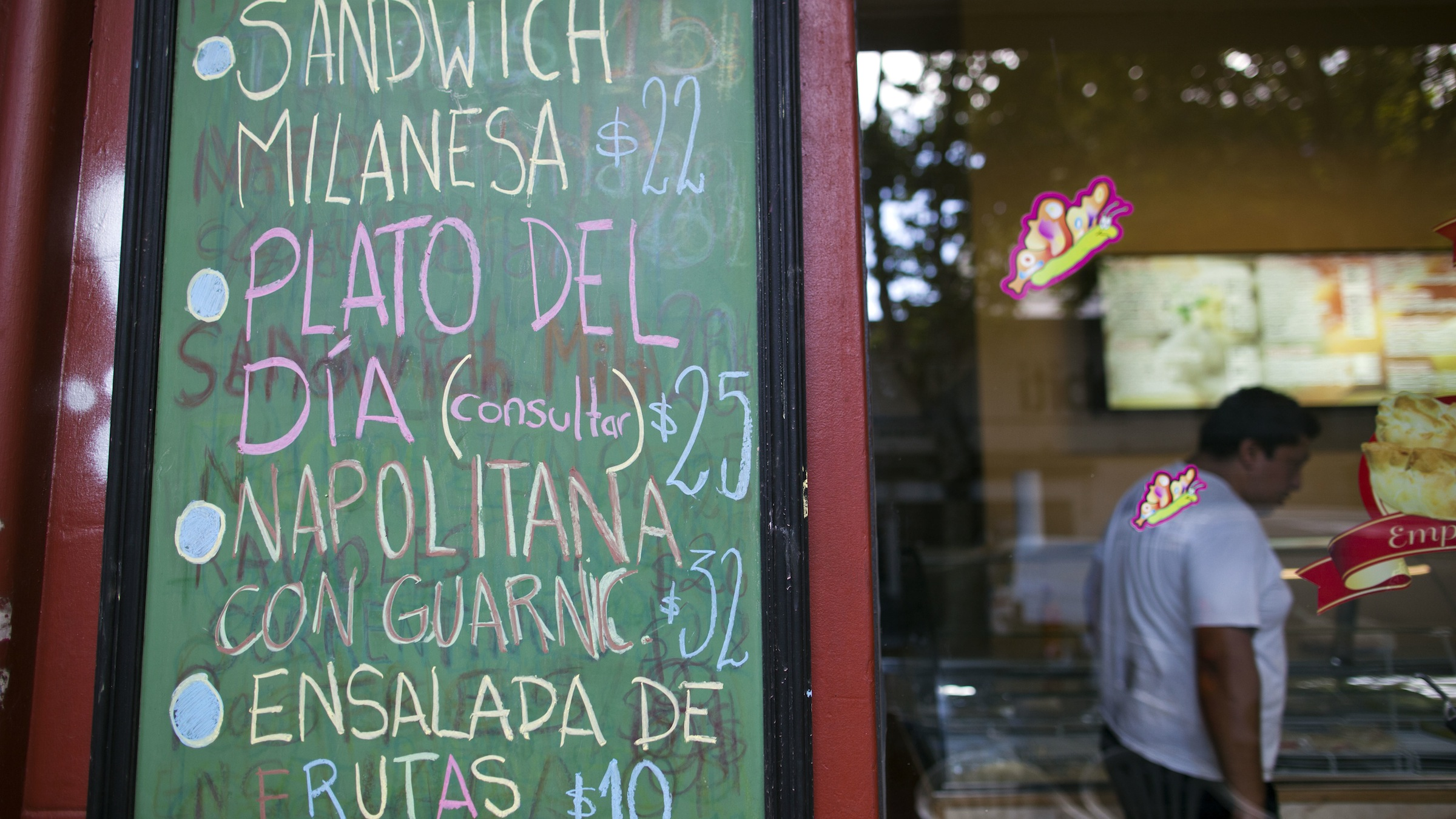 A deli sign advertises their prices in Buenos Aires, Argentina, Thursday, Jan. 17, 2013. It advertises a meat sandwich for 22 pesos, the meal of the day for 25 pesos, a meat plate with ham and cheese for 32 pesos and a fruit salad for 10 pesos.  The nation's currency's official rate is 4.96 pesos per 1 US dollar, and the black market rate is about 7.50 pesos per 1 US dollar.  Close government allies have given up defending the official statistics service, known as INDEC, which announced Monday that Argentinaís annual inflation was just 10.8 percent in 2012. Private economists have estimated that Argentinaís inflation was actually 26 percent or more, making it the worst in all of Latin America. (AP Photo/Natacha Pisarenko)