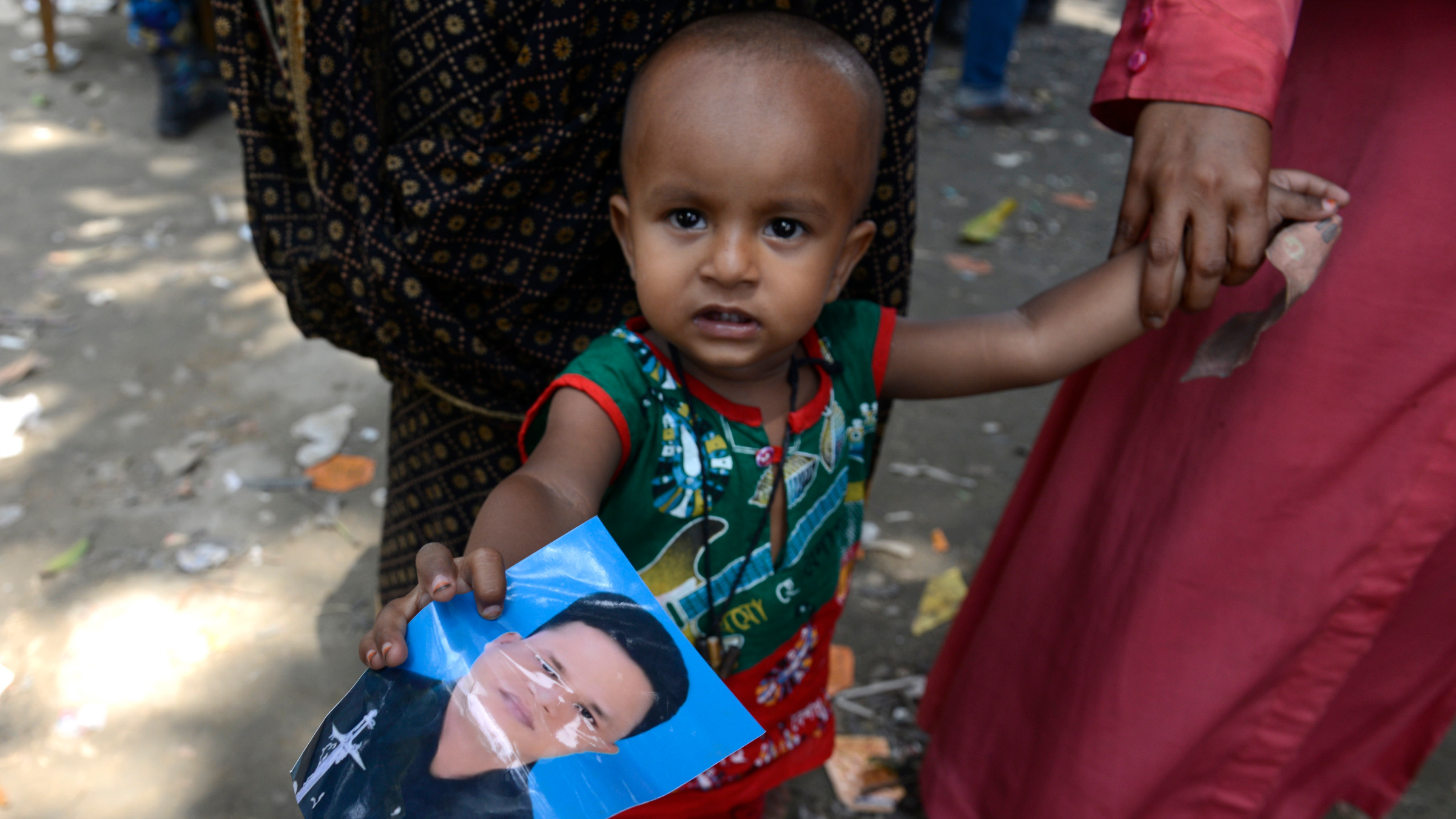 A Bangladeshi boy holds a photo of father