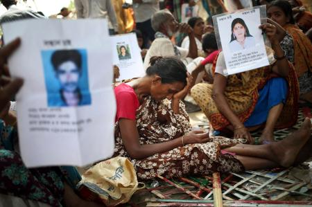 A woman grieves while others hold up pictures of their missing relatives.