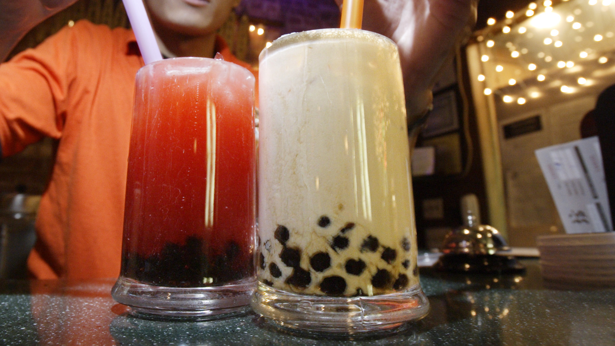 Jim He, of the Green Tea Cafe serves up glasses of bubble tea on Mott Street in the Chinatown neighborhood of New York Friday, Jan. 14, 2005. An Asian fad, the milky tea with little balls of tapioca has quickly become a feature attraction in a trip to Chinatown. (AP Photo/Gregory Bull