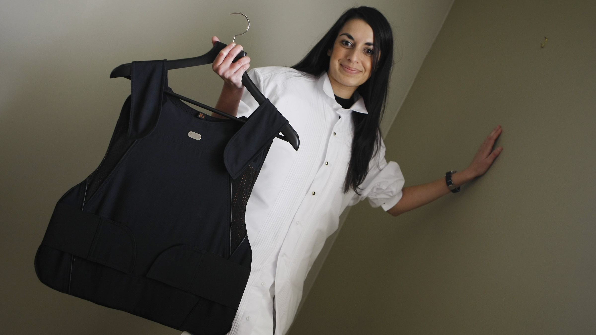 This photo taken Sept. 10, 2009 shows  Marisha Kelly, wearing a men's white bullet proof tuxedo shirt as she displays an Interior Vest, while posing  in Miami. The level IIIA protection clothing was made by Miguel Caballero from Colombia, which is now being sold primarily to clients from South America.  (AP Photo/J. Pat Carter)
