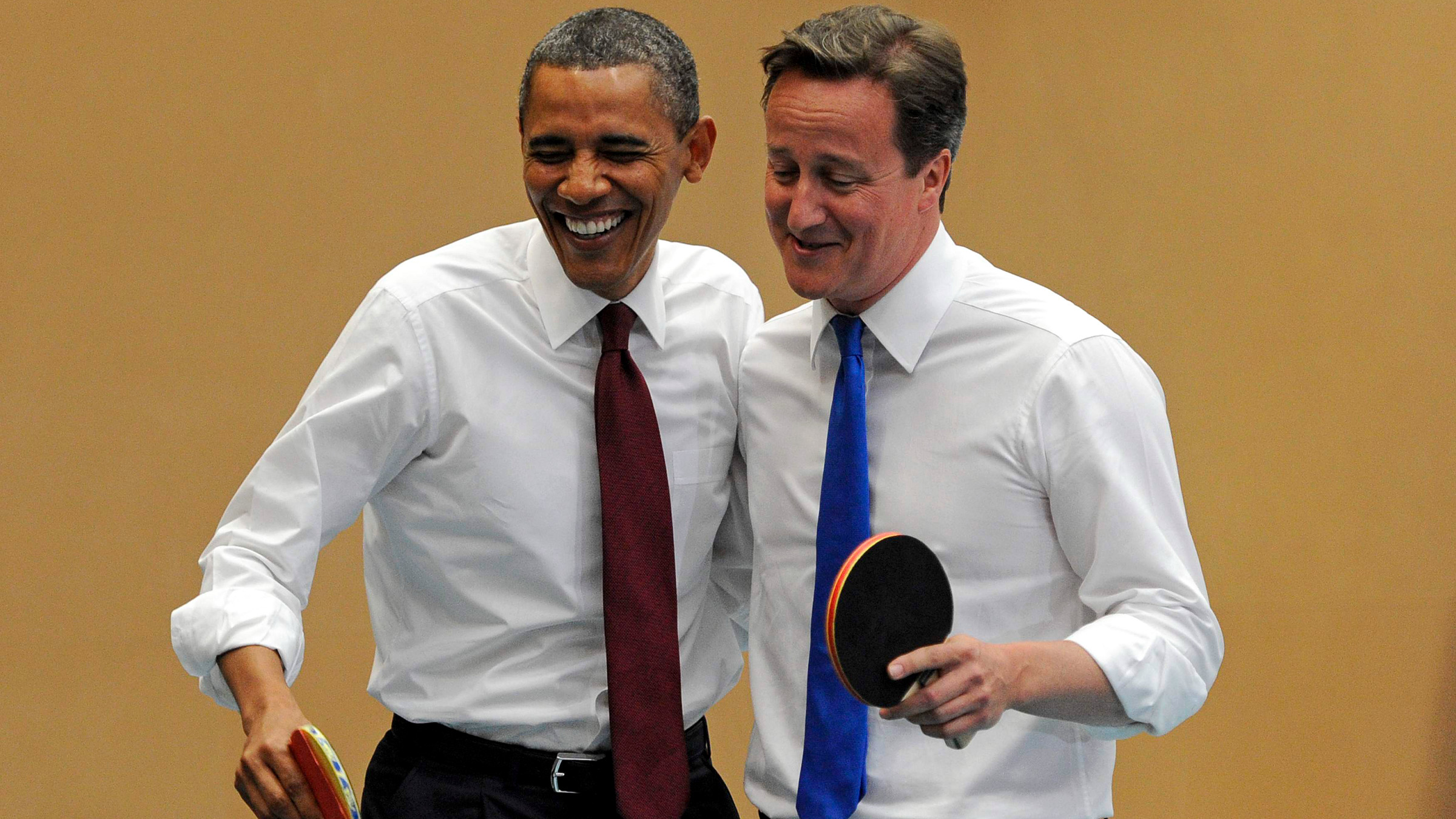 U.S. President Barack Obama, left, and Britain's Prime Minister David Cameron laugh as they play table tennis at Globe Academy, in south London Tuesday May 24, 2011.